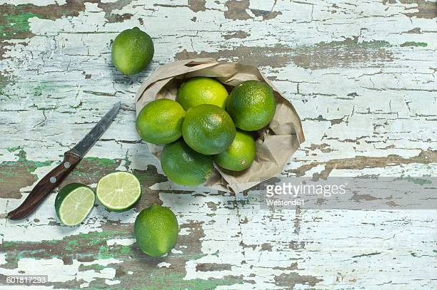 Whole and sliced limes and kitchen knife on paper bag and wood