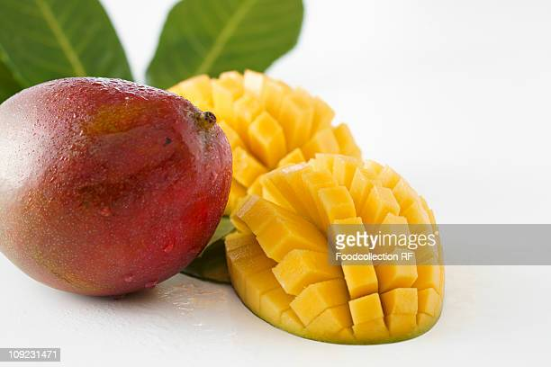 Whole and sliced mangos on white background, close-up