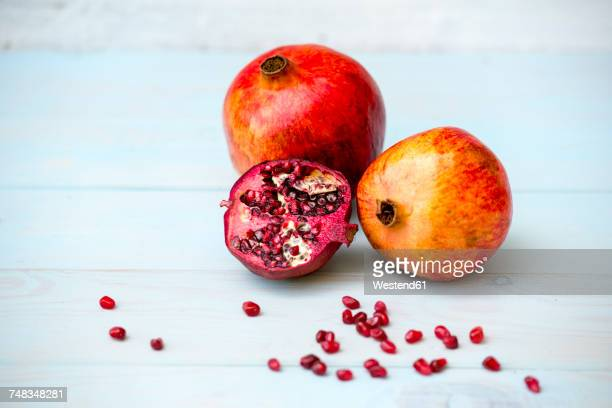 Whole and sliced omegranate and pomegranate seeds on wood