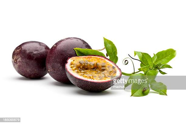 Whole and sliced passion fruits with leaves and tendrils