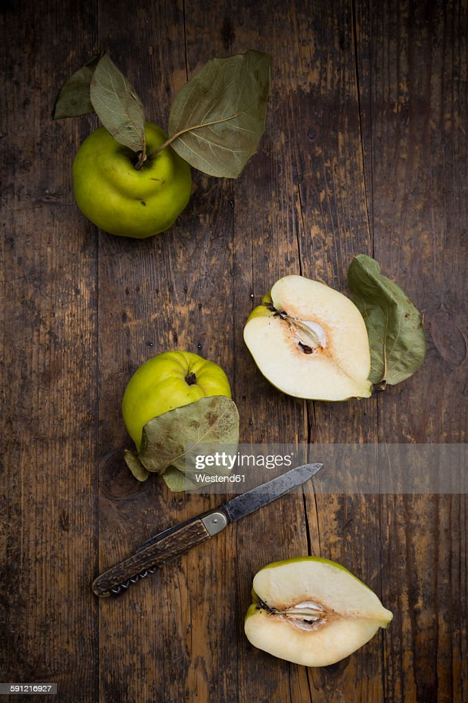 Whole and sliced quinces and a pocket knife on wood