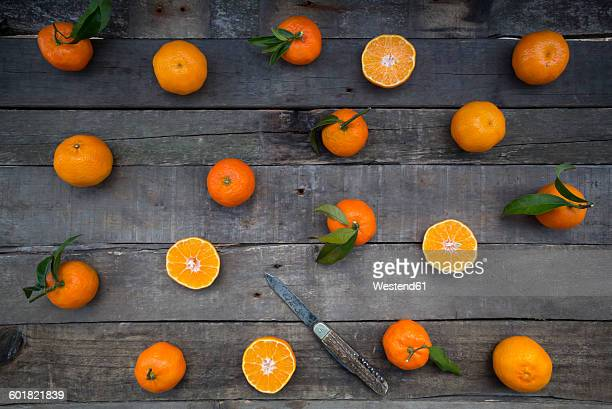 Whole and sliced tangerines and a knife on wood