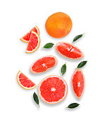 whole and slices grapefruit with green leaves isolated on white background, flat lay, top view