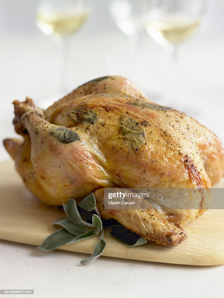 Whole chicken baked with herbs on cutting board, close-up : Stock Photo