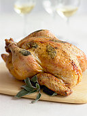 Whole chicken baked with herbs on cutting board, close-up