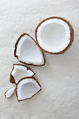 Pieces of a whole raw coconut cracked open on a white background and viewed from above