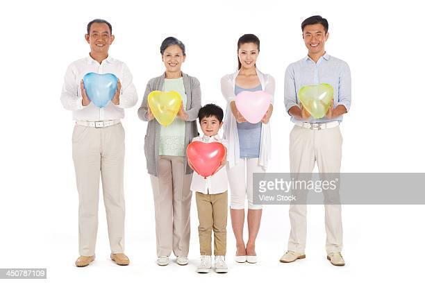 Whole family holding heart-shaped balloon