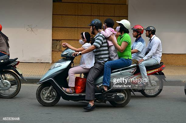 A whole family of four riding on a motor scooter in a busy street scene in Hanoi