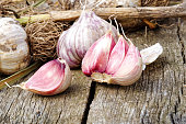 Whole garlic with broken bulb and pink cloves on rustic wooden board.