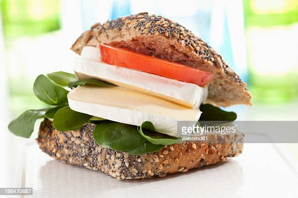 Whole grain bread with soft cheese, tomato and lamb's lettuce on chopping board, close up
