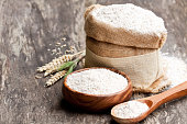 Whole  grain flour in a wooden bowl and sackcloth bagwith ears