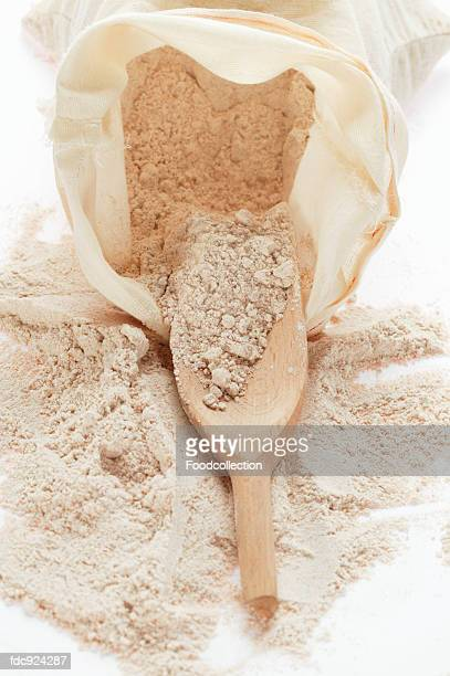 Whole meal flour in sack with wooden scoop