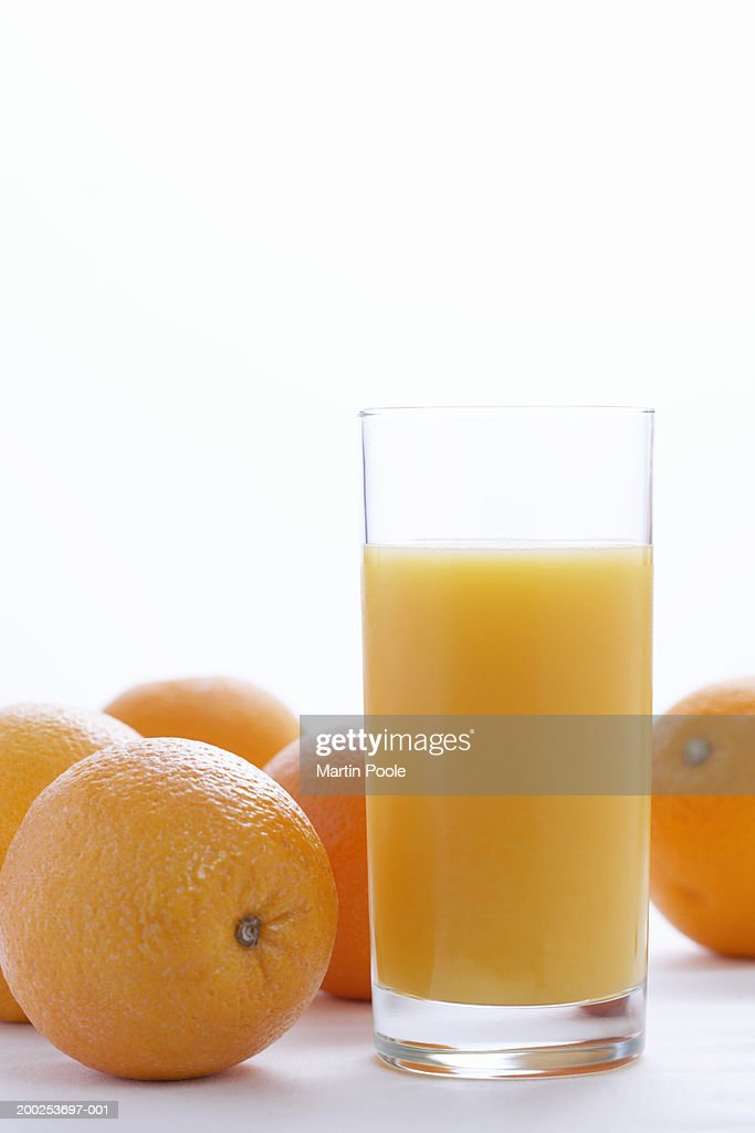 Whole oranges by orange juice in glass, close-up : Stock Photo