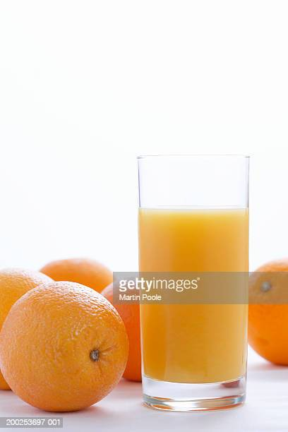 Whole oranges by orange juice in glass, close-up