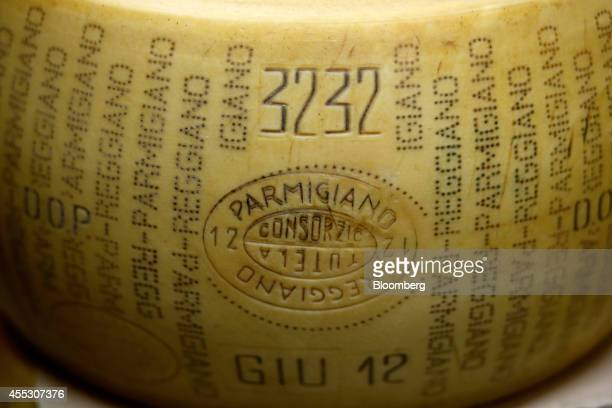 A whole ParmigianoReggiano cheese sits on a storage rack during the aging process at Coduro cheesemakers in Fidenza Italy on Thursday Sept 11 2014...