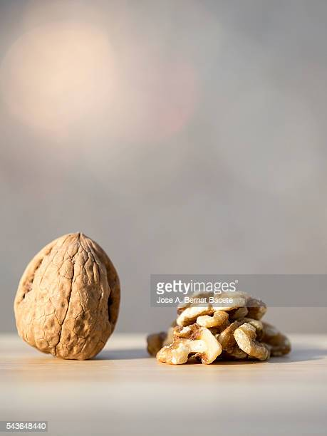 Whole peeled walnut and walnut on a wooden table illuminated by sunlight