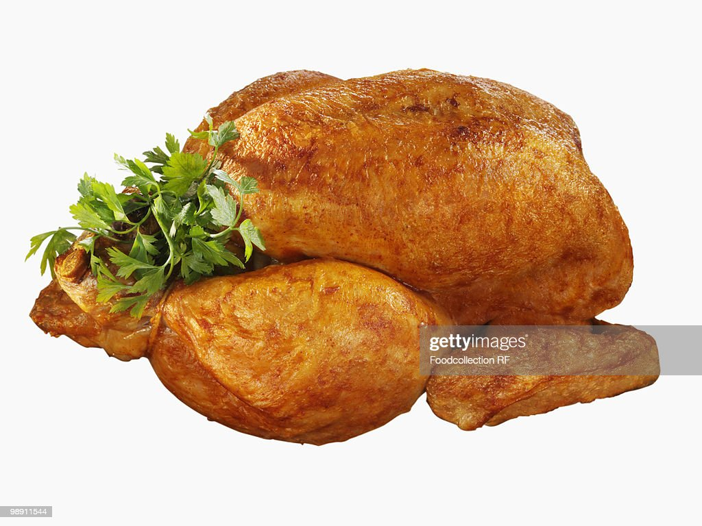 Whole roast chicken with parsley against white background, close-up : Stock Photo