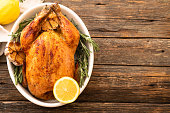 Whole roasted chicken with lemon and rosemary on a plate. Rustic style.
