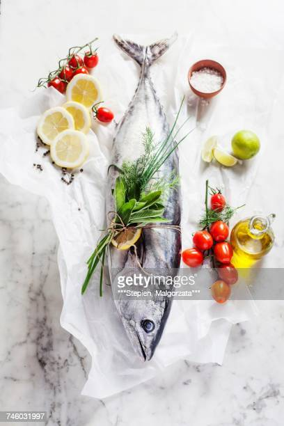 A whole tuna fish, cherry tomatoes, a bunch of herbs, lemons, olive oil and salt