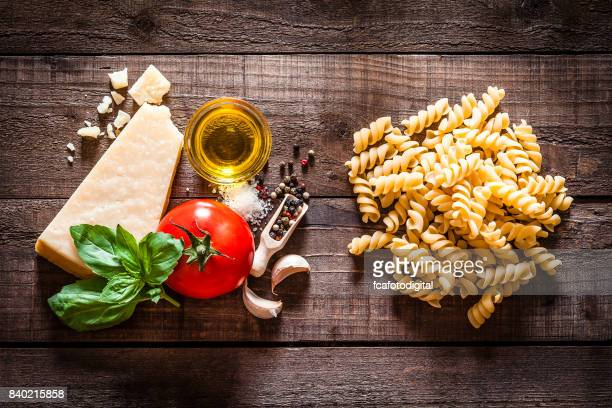 Wholegrain penne with ingredients on rustic wooden table