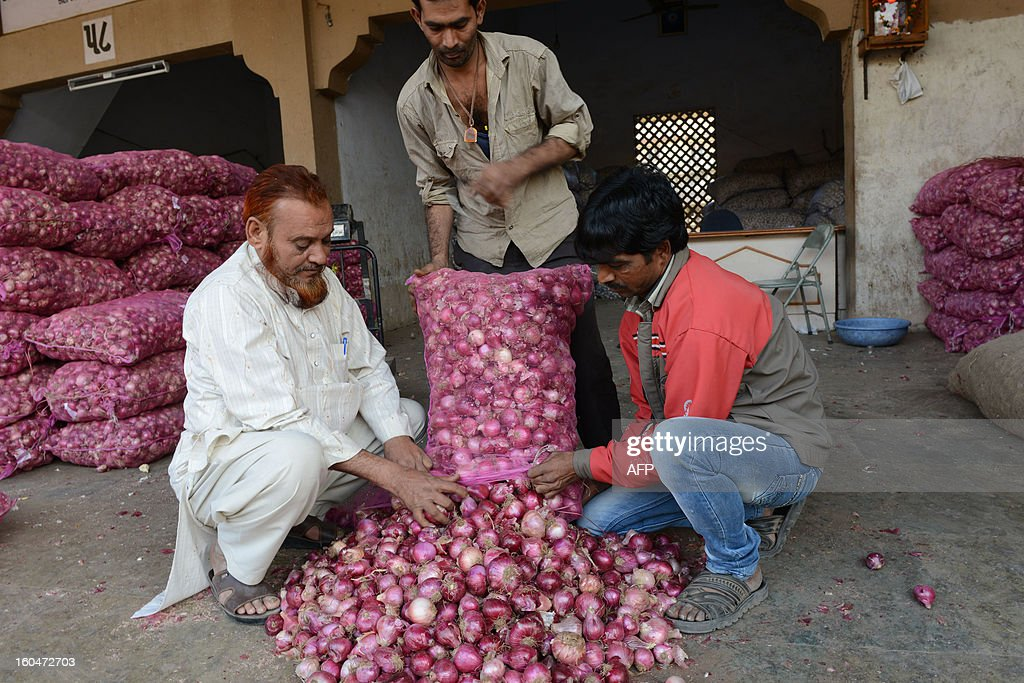 Wholesale onion trader Anwarbhai (L) shows his produce to a prospective customer at the Agricultural Produce Market Committee (APMC) in Ahmedabad on February 1, 2013. Worried over the skyrocketing onion prices in the election year, the Delhi Government has urged Union Agriculture Minister Sharad Pawar to restraint export of onion. The prices of onion have nearly tripled in the past one week in retail market due to short supply and poor crops in Maharashtra and Gujarat. AFP PHOTO / Sam PANTHAKY