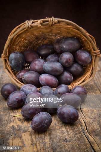 Wicker basket of plums on wooden table