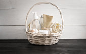 Wicker basket with spa treatments on wooden table. Still life