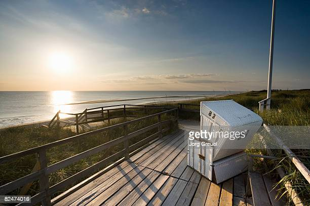 Wicker beach chair at sunset