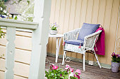 Wicker chair with potted plants on porch