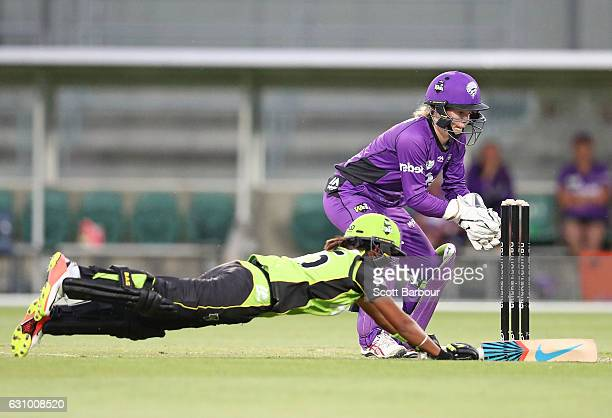 Wicketkeeper Georgia Redmayne of the Hurricanes attempts to run out Harmanpreet Kaur of the Thunder during the Women's Big Bash League match between...