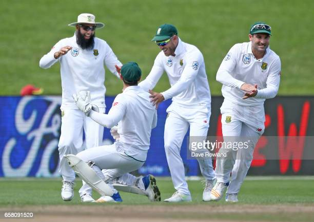 Wicketkeeper Quinton de Kock is congratulated by Captain Faf du Plessis of South Africa for taking the wicket Tom Latham of New Zealand during day...
