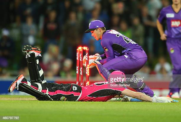 Wicketkeeper Tim Paine of the Hurricanes unsuccessfully attempts to run out Riki Wessels of the Sixers during the Big Bash League match between the...