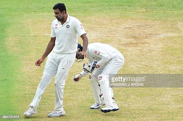Wicketkeeper Wriddhiman Saha of India collides with teammate bowler Ravichandran Ashwin of India following a shot by Marlon Sammuels of the West...