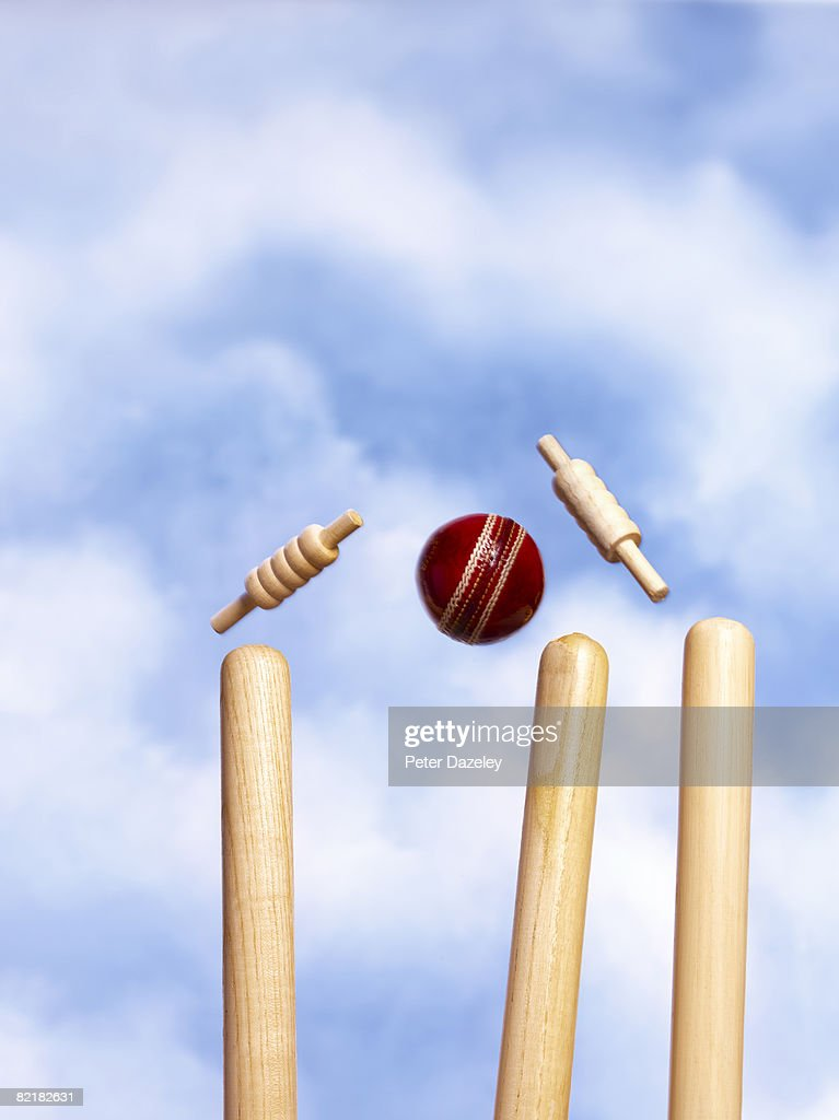 Wickets being knocked of stumps against blue sky