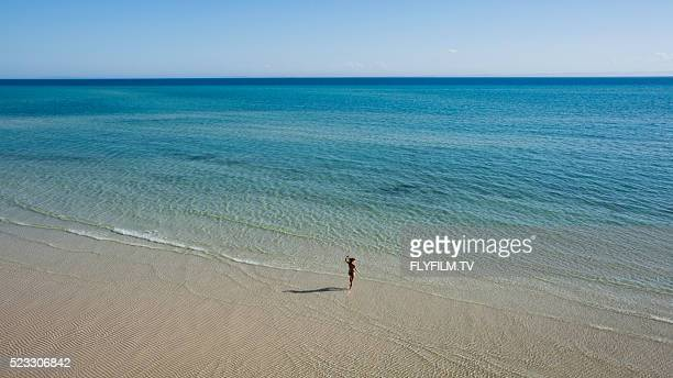Wide aerial shot of nondescript girl jumping on beach