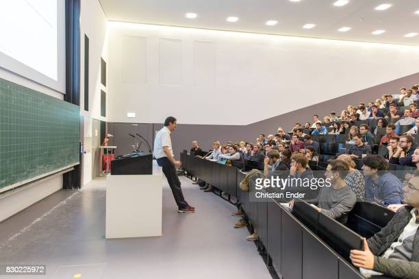 Wide angle from the left to the right Displaying a professor holding a presentation in front of a lecture hall with students at the technical...