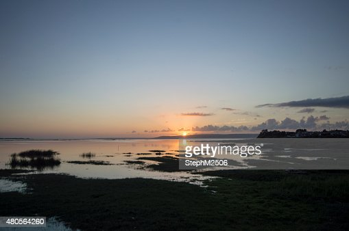 Wide angle landscape image of a sunset over marsh land : Stock Photo