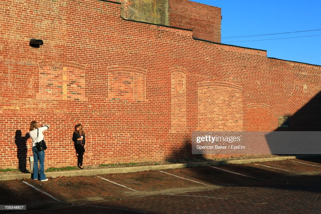 Wide Angle Of Two Girls Taking Pictures Against Brick Wall : Stock Photo