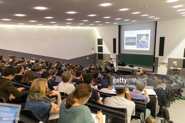 Wide angle tilt from the left to the right and then slightly up Displaying a lecture hall filled with students while a tutor is holding a...