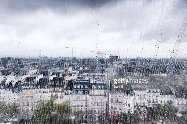 Large angle de vue de la ville par la fenêtre sous la pluie