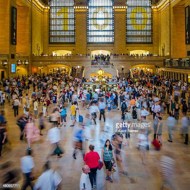 CONTENT] Wide angle view of Grand Central Terminal with time exposure showing people rushing around during 100th anniversary