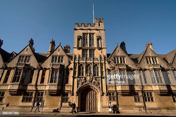 A wide angle view of the facade and gatehouse of Brasenose College glowing in the golden hour light on High Street in the University City of Oxford UK