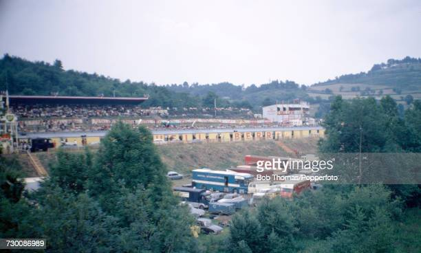 Wide angle view of the grandstand with trucks and support cars positioned in front of the track at the Circuit de Charade motorsport race track near...