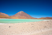 Wide angle view of the outstanding Green Lagoon or 'Laguna Verde', a frozen salt lake on the way to the famous Uyuni Salt Flat, travel destination in Bolivia. Snowcapped Licancabur Volcano, 5920 m, in