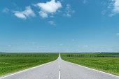 A wide asphalt road between green fields stretching into the blue sky