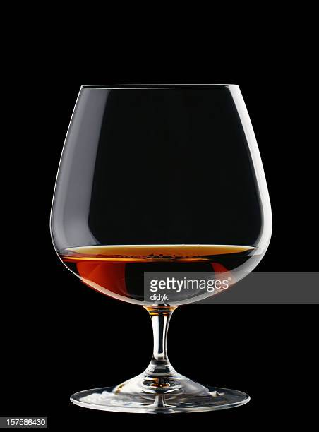 A wide glass of brandy isolated on a black background