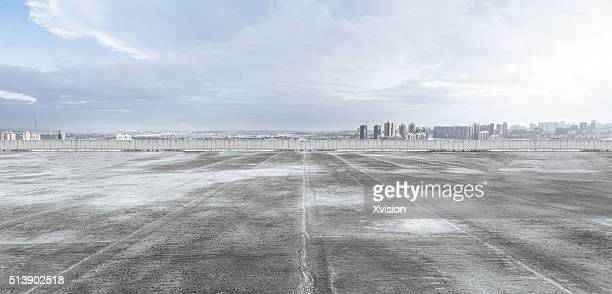 Wide open asphalt covered platform with Fuzhou cityscape at background under sunny day
