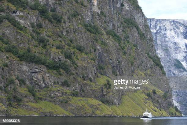 Wide photo of ferry sailing through the Norwegian fjord land along side tall cliff on February 8th 2017 in Norway