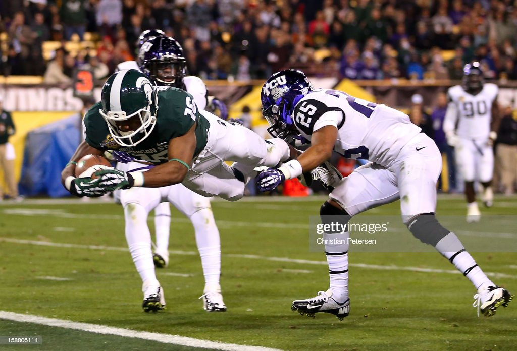 Wide receiver Aaron Burbridge #16 of the Michigan State Spartans dives into the end zone to score a 15 yard touchdown reception past cornerback Kevin White #25 of the TCU Horned Frogs during the thrid quarter of the Buffalo Wild Wings Bowl at Sun Devil Stadium on December 29, 2012 in Tempe, Arizona.