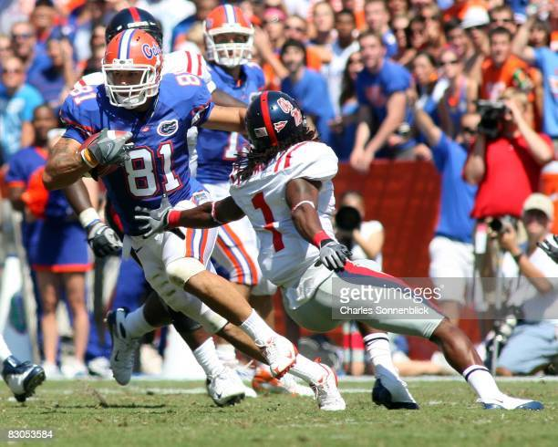 Wide receiver Aaron Hernandez of the Florida Gators catches a pass for a large gain while avoiding safety Kendrick Lewis of the Mississippi Rebels...